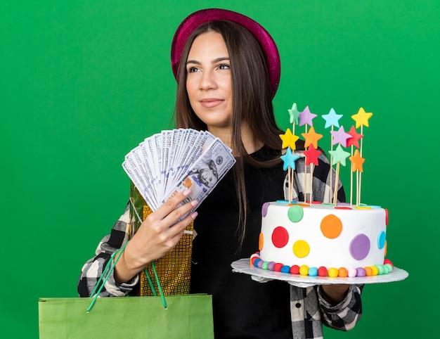 Piacere guardando lato giovane bella ragazza che indossa un cappello da festa tenendo la torta con borsa regalo e contanti