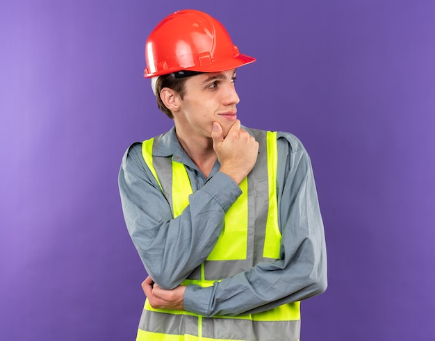 Lieto di guardare di lato il giovane costruttore in uniforme ha afferrato il mento