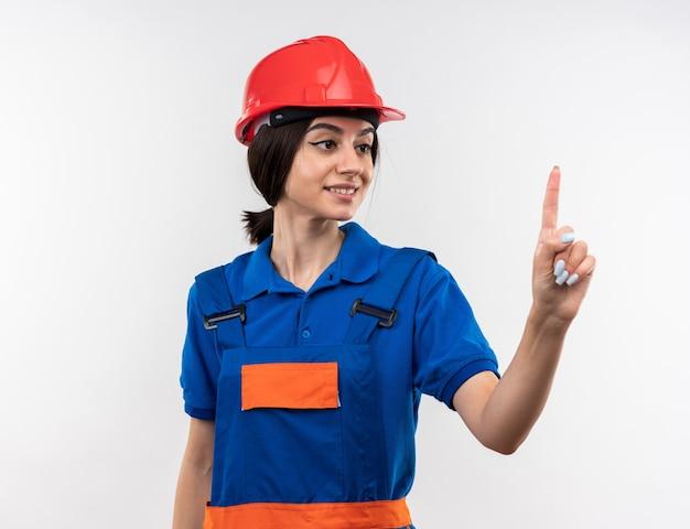 Lieto di guardare la giovane donna del costruttore in uniforme che ne mostra una isolata sul muro bianco