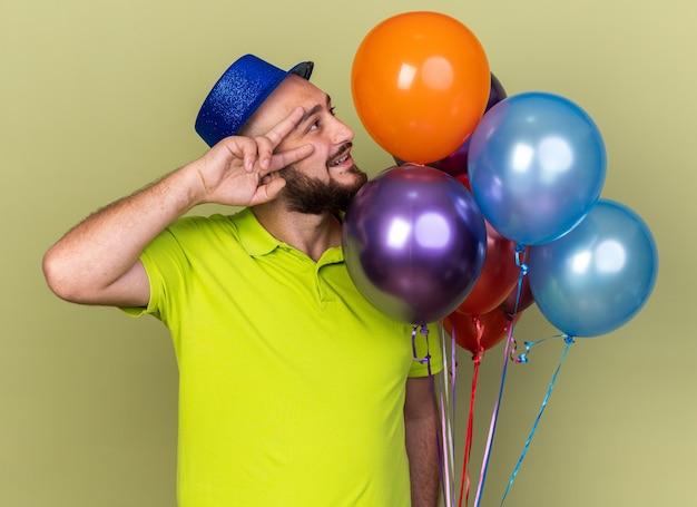 Felice guardando lato giovane che indossa un cappello da festa in piedi palloncini vicini che mostrano un gesto di pace