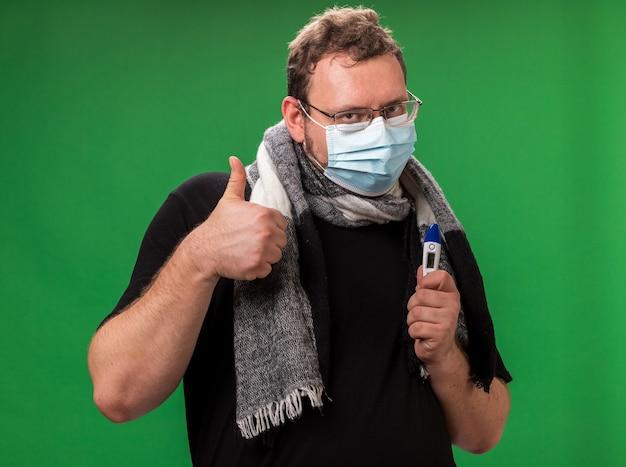 Felice maschio malato di mezza età che indossa maschera medica e sciarpa che tiene il termometro che mostra il pollice in su