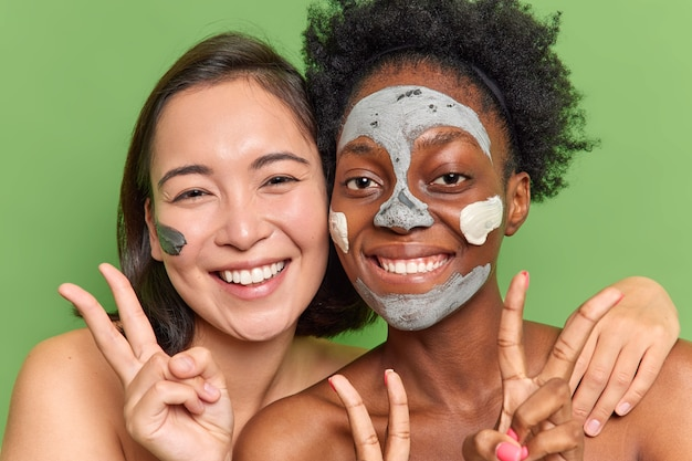 Le giovani donne multietniche soddisfatte stanno vicine l'una all'altra si divertono a sottoporsi a procedure di bellezza applicano maschere di argilla