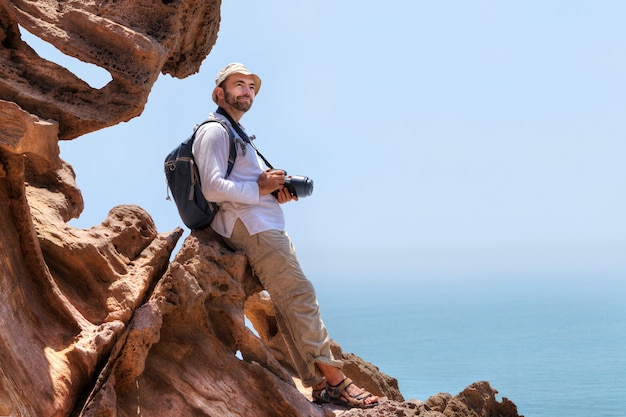 Il fotografo naturalista soddisfatto è seduto sul bordo della scogliera, isola di hormuz, hormozgan, iran.