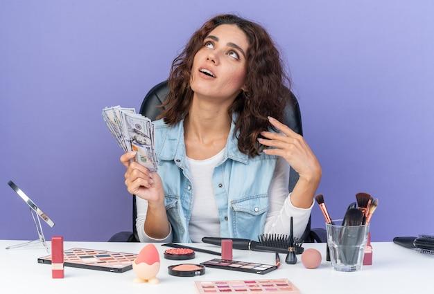 Donna abbastanza caucasica contenta seduta al tavolo con strumenti per il trucco in possesso di denaro e guardando in alto