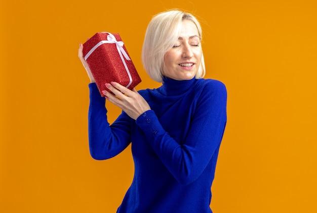 Piacevole donna slava che tiene in mano una confezione regalo isolata sulla parete arancione con spazio per le copie