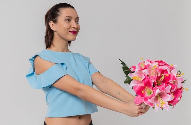 Una bella giovane donna contenta che tiene in mano un mazzo di fiori in piedi di lato