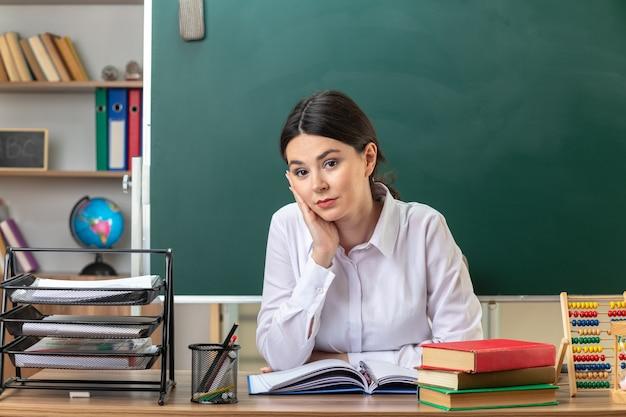 Felice di mettere la mano sulla guancia giovane insegnante seduta a tavola con gli strumenti della scuola in classe