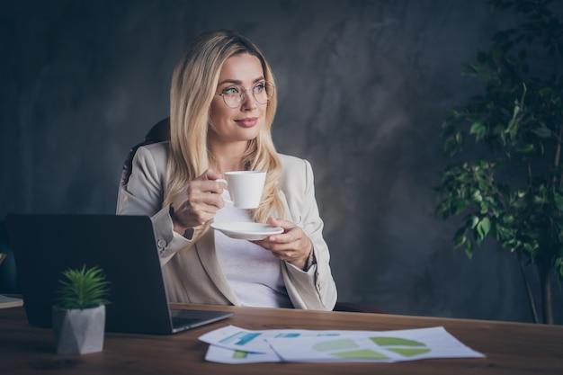 Soddisfatto soddisfatto sereno imprenditore calmo che riposa in spettacoli con una tazza di tè in mano godendosi la fine della giornata lavorativa