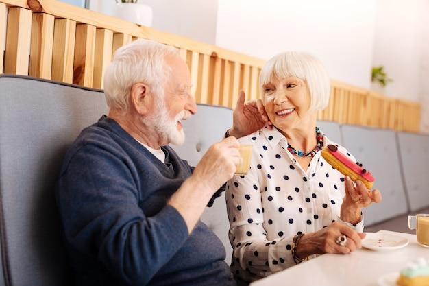 Felice donna senior holding eclair e uomo anziano che beve caffè