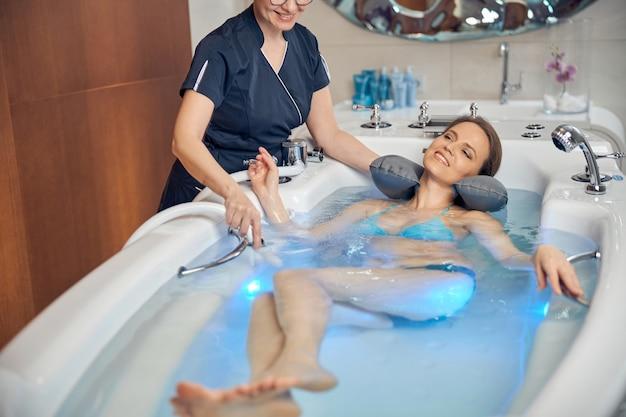 Paziente serena e soddisfatta che sorride durante la procedura balneologica eseguita da un terapista termale qualificato