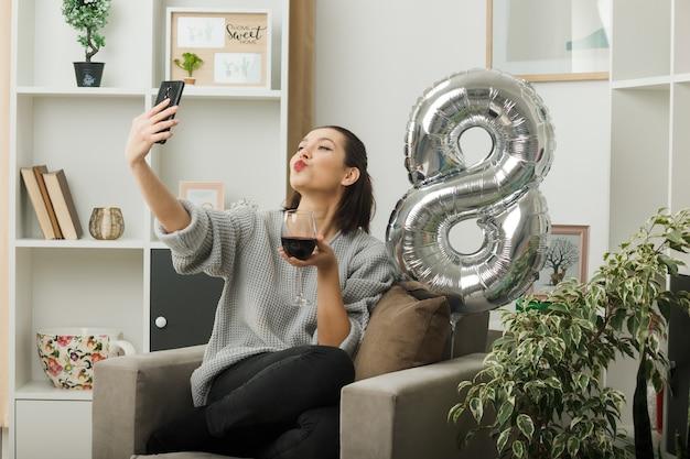 Piacere di mostrare il gesto del bacio bella donna durante la felice giornata delle donne con in mano un bicchiere di vino prendi un selfie seduto sulla poltrona in soggiorno