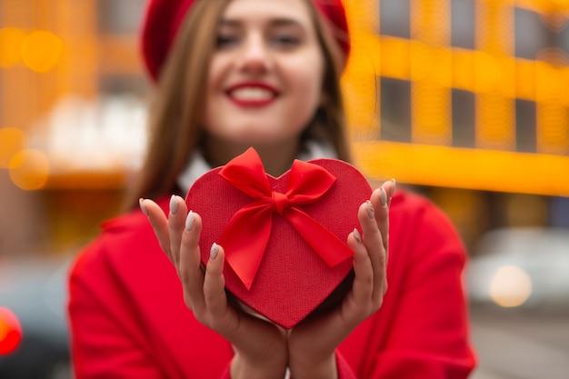 Piacevole donna sorridente che tiene in mano una confezione regalo di san valentino a forma di cuore su uno sfondo di città di luci sfocate. colpo del primo piano. sfondo sfocato con bokeh