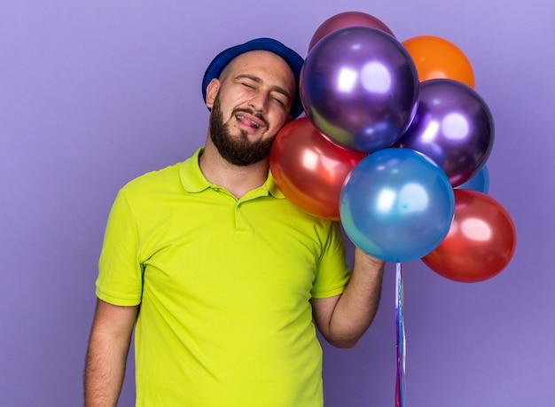 Soddisfatto del giovane con gli occhi chiusi che indossa un cappello da festa con palloncini che mostrano la lingua isolata sulla parete blu