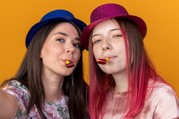 Donne soddisfatte che indossano il cappello da festa che soffiano il fischio della festa tenendo la telecamera isolata sulla parete arancione