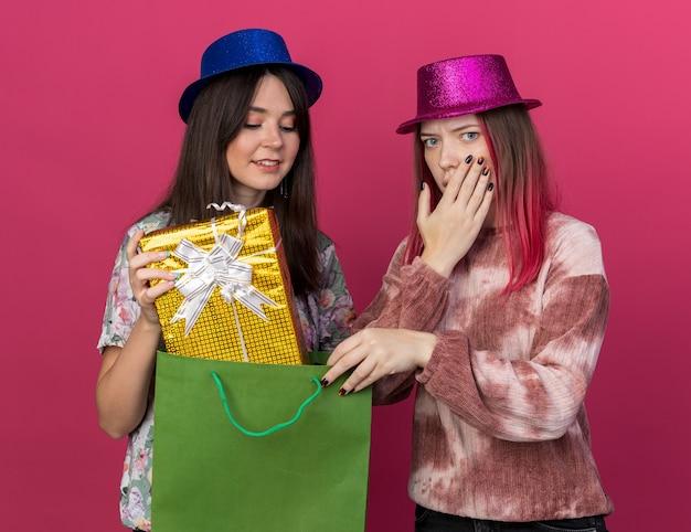 Donne soddisfatte che indossano un cappello da festa con una borsa regalo isolata su una parete rosa
