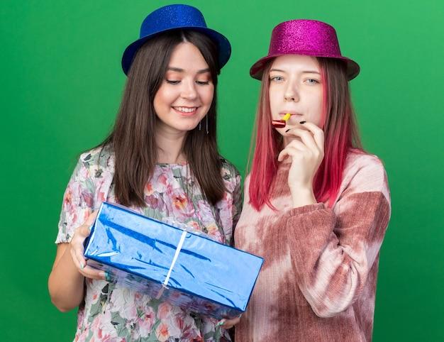 Donne soddisfatte che indossano un cappello da festa che tengono una confezione regalo e soffiano un fischietto da festa isolato su una parete verde