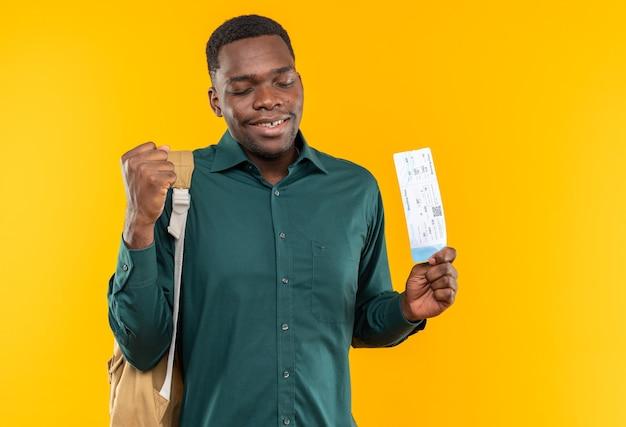 Felice giovane studente afroamericano con lo zaino che tiene il biglietto aereo e tiene il pugno isolato sul muro arancione con spazio per le copie