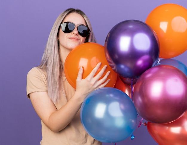 Lieta giovane bella ragazza con gli occhiali che tengono palloncini isolati sulla parete blu