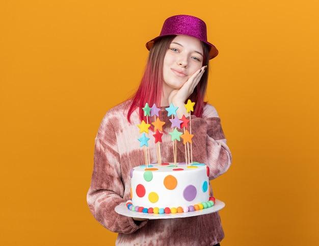 Lieta giovane bella ragazza che indossa cappello da festa tenendo la torta mettendo la mano sulla guancia isolata sulla parete arancione