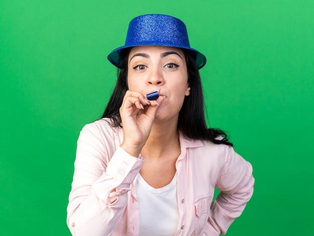 Felice giovane bella donna che indossa cappello da festa che soffia fischio di festa mettendo la mano sull'anca