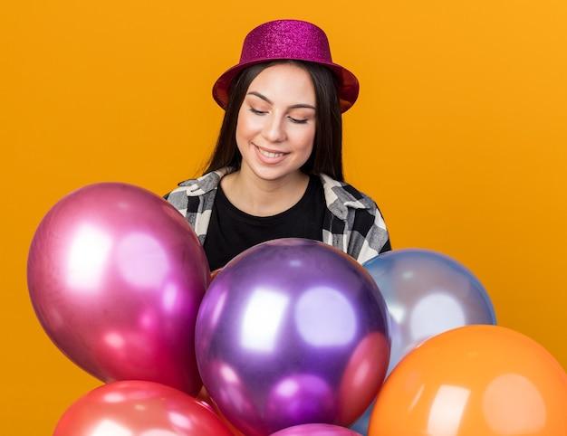Felice giovane bella donna che indossa un cappello da festa in piedi dietro palloncini isolati su una parete arancione