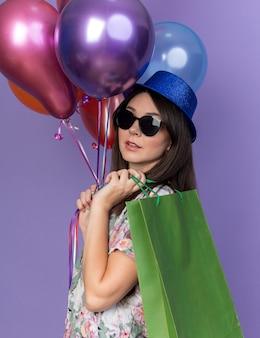 Piacevole giovane bella donna che indossa un cappello da festa con occhiali che tengono palloncini con sacchetto regalo isolato su parete blu