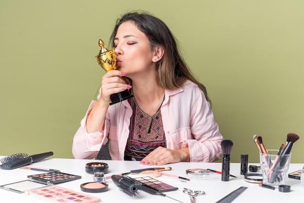 Felice giovane ragazza bruna seduta al tavolo con strumenti per il trucco che tiene e bacia la tazza del vincitore