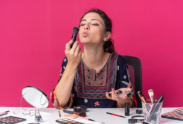 Felice giovane ragazza bruna seduta al tavolo con strumenti per il trucco che tiene e guarda il pennello per il trucco isolato sulla parete rosa con spazio per le copie