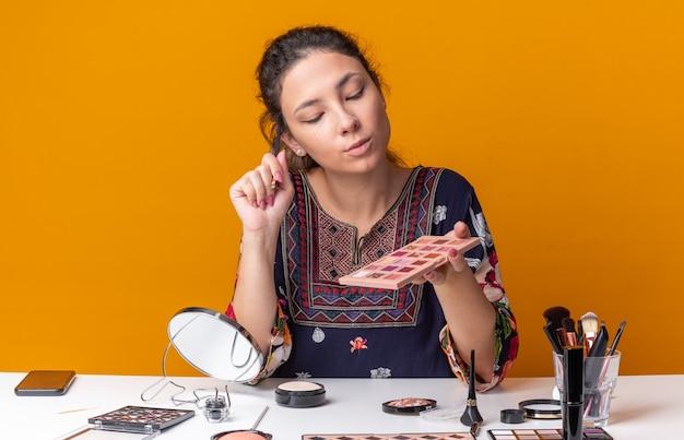 Felice giovane ragazza bruna seduta al tavolo con strumenti per il trucco che tiene il pennello per il trucco e guarda la tavolozza dell'ombretto isolata sulla parete arancione con spazio per le copie
