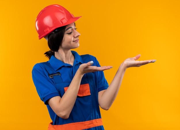 Felice giovane donna costruttore in uniforme che finge di tenere e indica qualcosa di isolato sul muro giallo con spazio di copia
