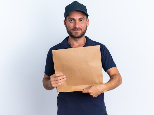 Felice giovane fattorino caucasico in uniforme blu e berretto con in mano un pacchetto di carta