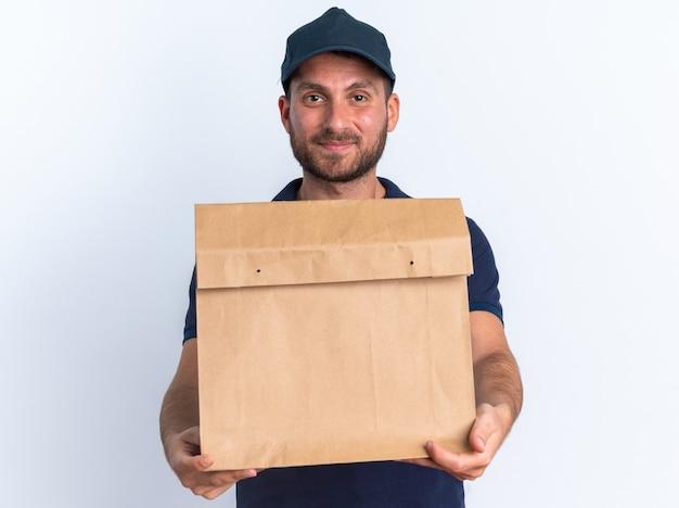 Felice giovane fattorino caucasico in uniforme blu e berretto guardando la telecamera che allunga il pacchetto di carta verso la telecamera isolata sul muro bianco