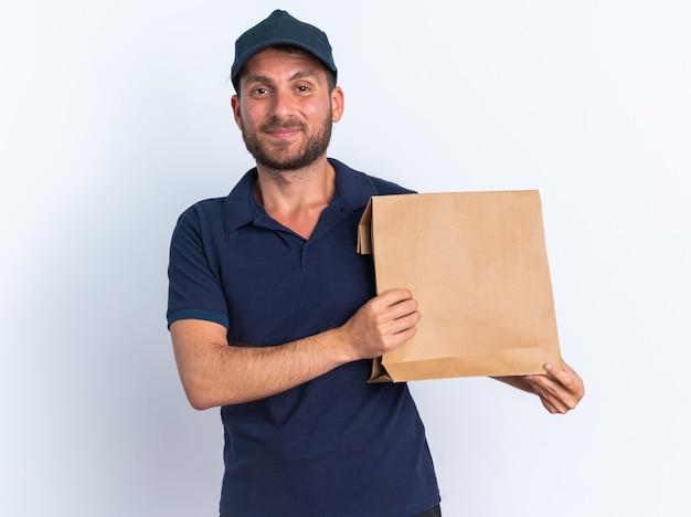 Felice giovane fattorino caucasico in uniforme blu e cappuccio che mostra il pacchetto di carta guardando la telecamera isolata sul muro bianco