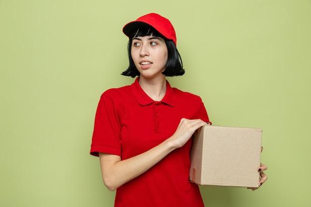 Felice giovane donna delle consegne caucasica che tiene in mano una scatola di cartone e guarda di lato