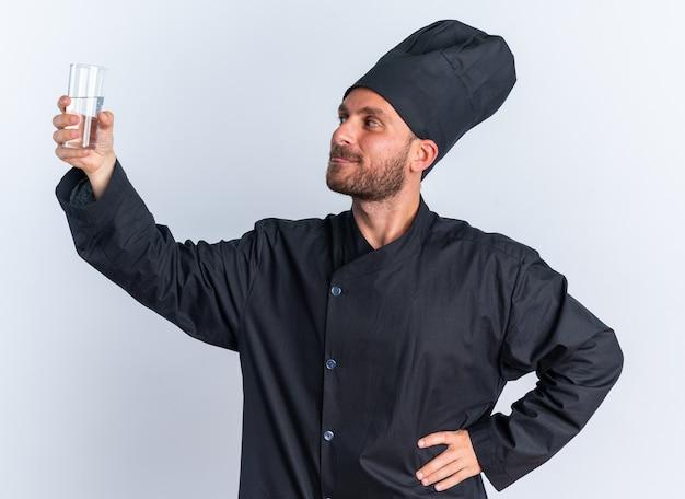 Felice giovane maschio caucasico cuoco in uniforme da chef e berretto tenendo la mano sulla vita alzando e guardando il bicchiere d'acqua che mostra la lingua isolata sul muro bianco
