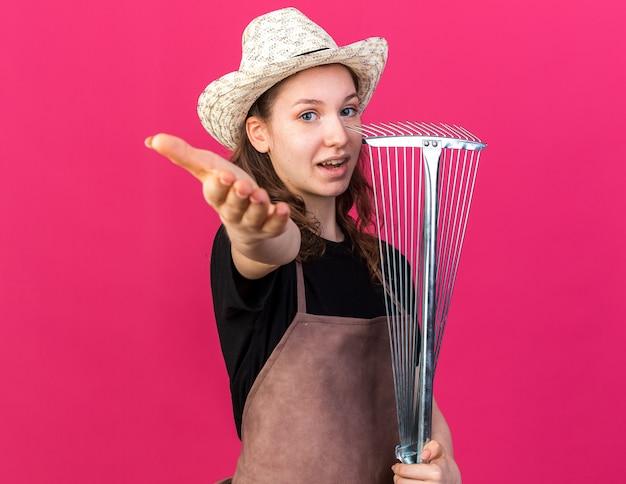 Felice giovane giardiniere femminile che indossa un cappello da giardinaggio tenendo il rastrello delle foglie e tendendo la mano alla telecamera