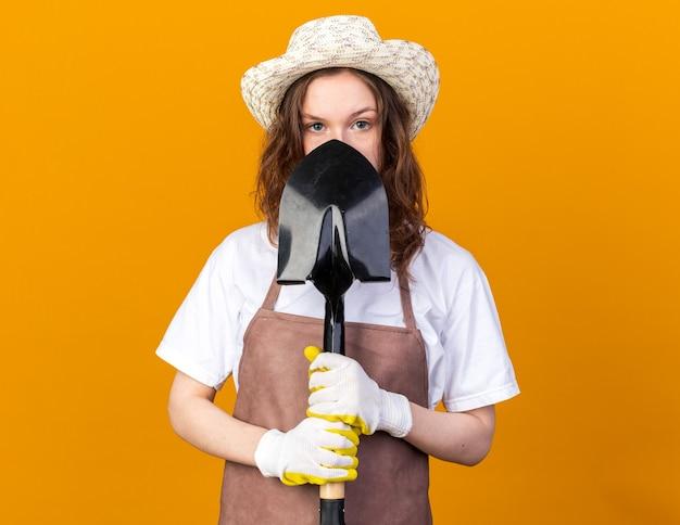 Felice giovane giardiniere femminile che indossa un cappello da giardinaggio con guanti faccia coperta con una vanga isolata sulla parete arancione
