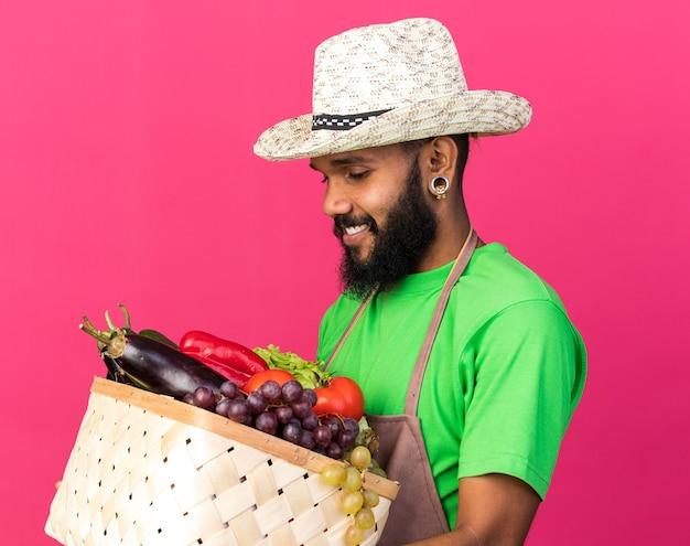 Felice giovane giardiniere afro-americano che indossa un cappello da giardinaggio che tiene e guarda un cesto di verdure