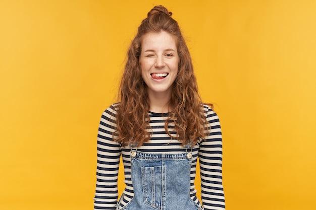 Soddisfatta giovane donna allo zenzero, indossa una salopette di jeans e una camicia spogliata, strizza l'occhio mentre flirta con il suo ragazzo, mostrando la lingua e sorride. isolato su muro giallo