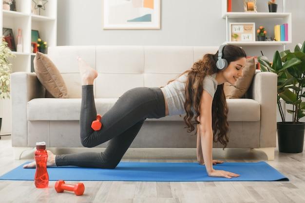 Felice ragazza che indossa le cuffie che si esercita con il manubrio sul materassino yoga davanti al divano nel soggiorno