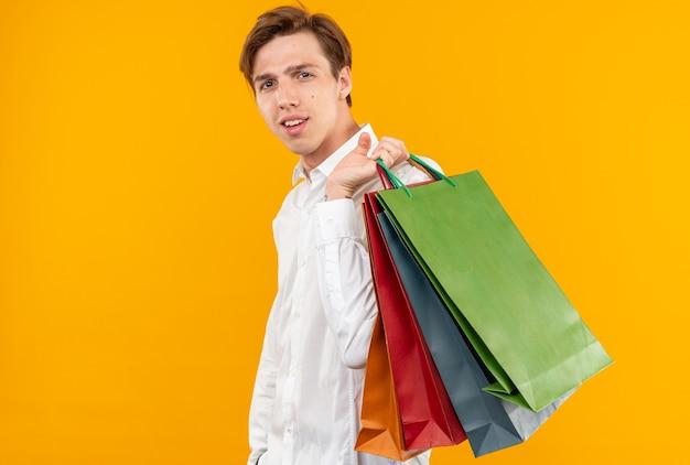 Lieto giovane bel ragazzo che indossa una camicia bianca che tiene borse sulla spalla isolata sulla parete arancione con spazio di copia