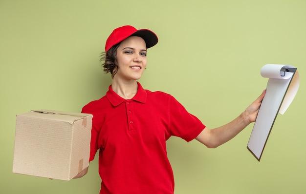 Lieta giovane graziosa donna delle consegne che tiene in mano una scatola di cartone e appunti