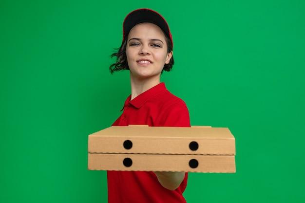 Lieta giovane bella donna delle consegne che porge scatole di pizza