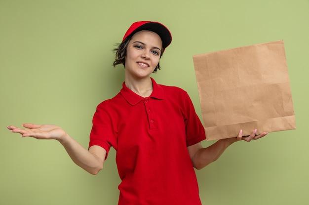 Felice giovane e graziosa donna delle consegne che tiene in mano imballaggi alimentari di carta e tiene la mano aperta