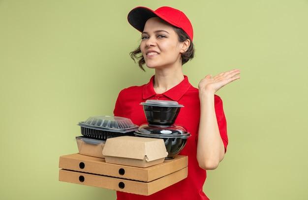 Lieta giovane bella donna delle consegne in piedi con la mano alzata e tenendo contenitori per alimenti con imballaggi su scatole per pizza