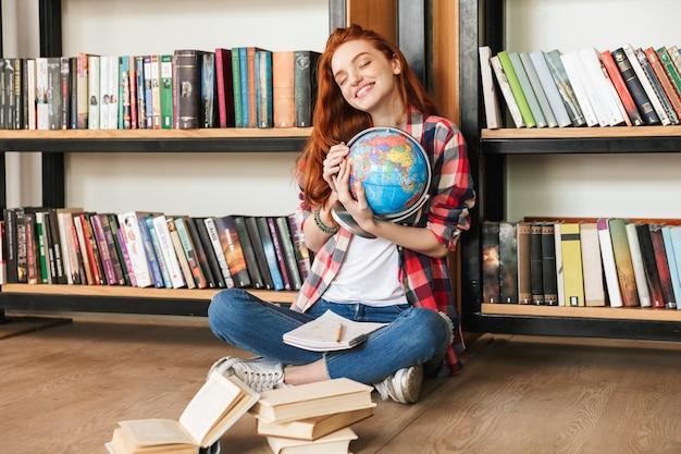Felice giovane bella signora rossa seduta in biblioteca