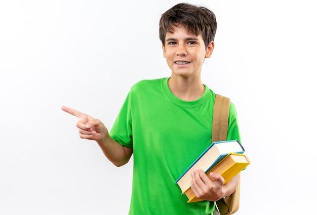 Felice giovane ragazzo della scuola che indossa uno zaino con libri punti a lato isolato sul muro bianco con spazio di copia