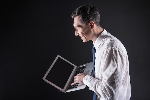 Piacevole esperienza. uomo bello positivo felice che tiene un laptop e guarda lo schermo del computer pur essendo di ottimo umore