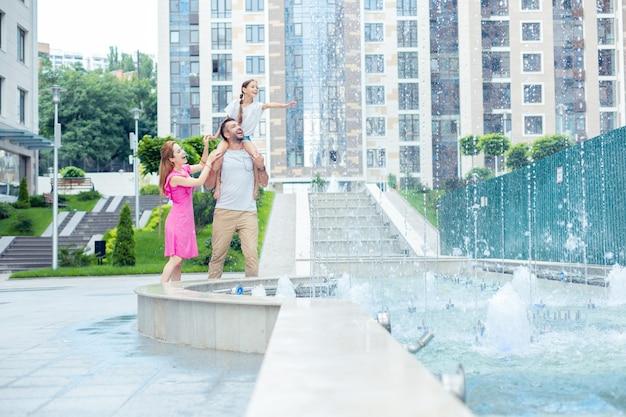 Tempo piacevole. bella famiglia allegra che guarda la fontana mentre fa una passeggiata serale lungo il quartiere