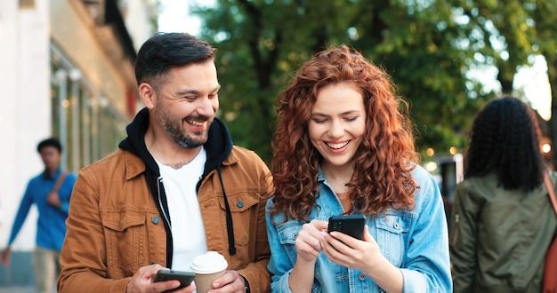 Piacere di camminare. coppia caucasica innamorata o amici che camminano per la strada, chiacchierano di piacere e bevono caffè mentre si sentono benissimo durante le vacanze estive